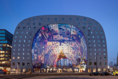 MVRDV's Markthal Rotterdam lit up by a colorful mural projected on its ceiling, created by artists Arno Coenen and Iris Roskam