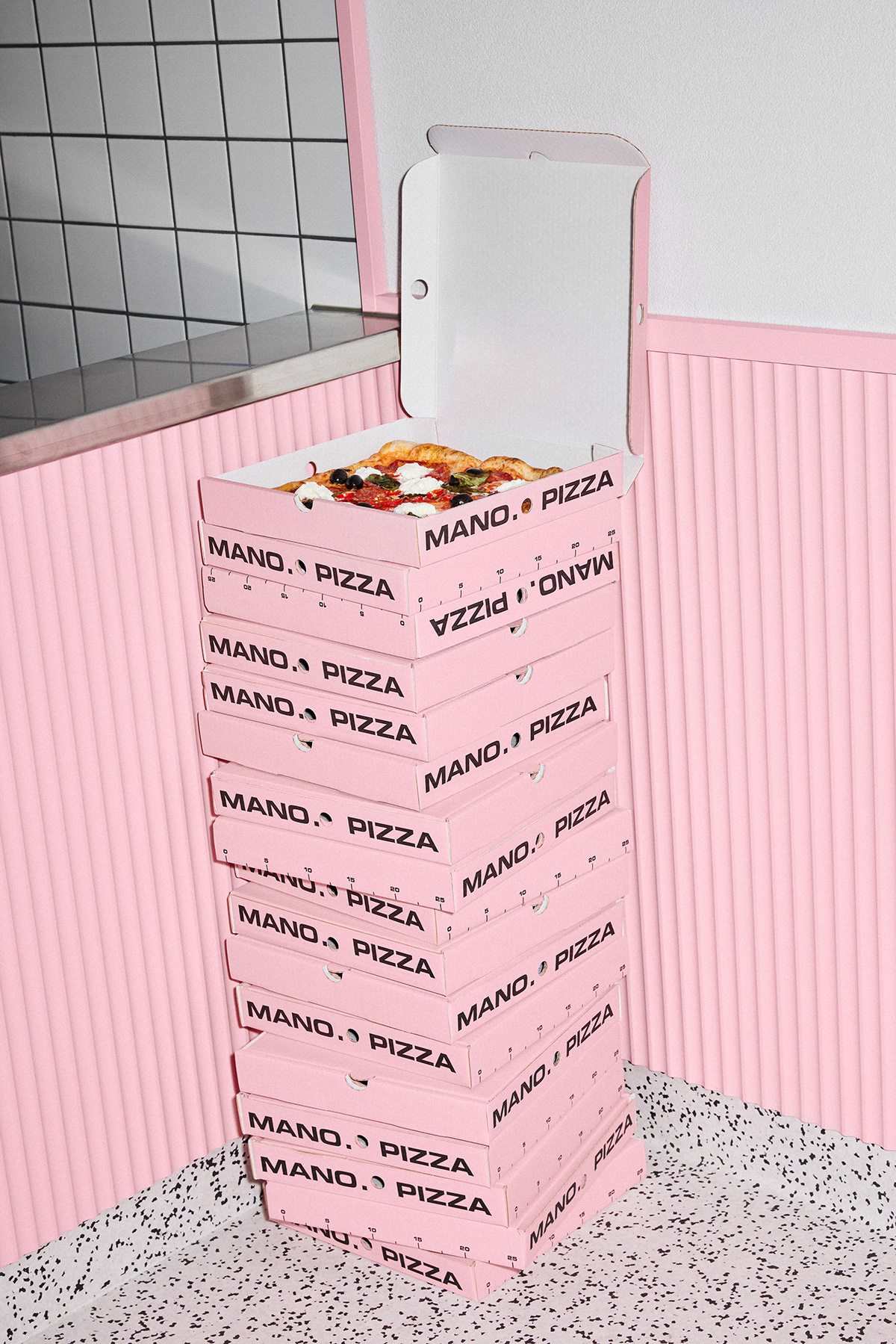 A stack of pink pizza boxes with